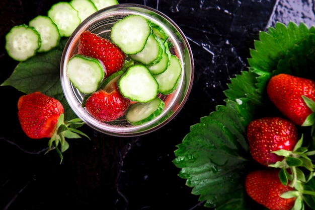 Cucumber and strawberry detox water in glass on black . diet. top view.