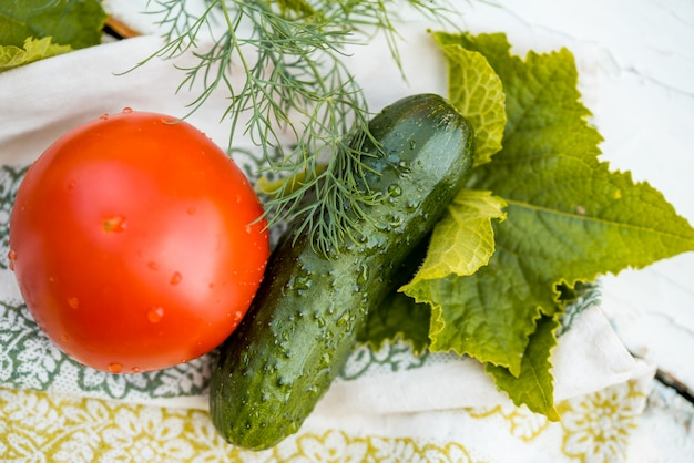 Cucumber and tomato and dill on a linen napkin with embroidery. fresh vegetables from the garden. leaves of greenery.
