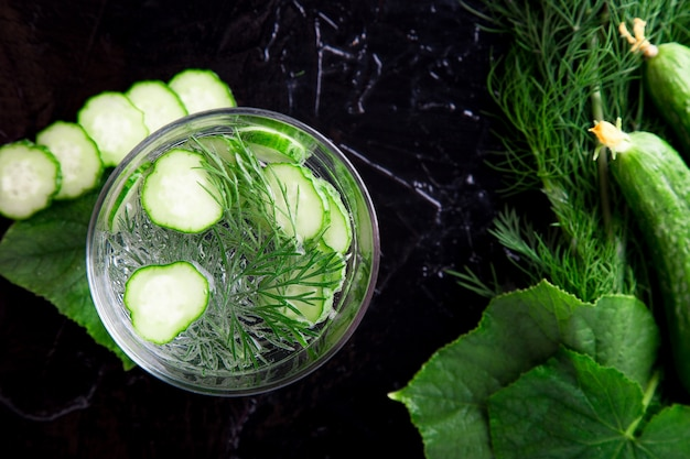 Cucumber water in glass with dill on black . detox, diet. backlight. top view. copyspace.