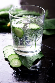 Cucumber water in glass with dill on black . detox, diet. backlight.