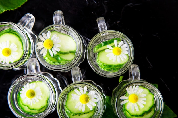 Cucumber water in six little mason glass jar on black . top view.