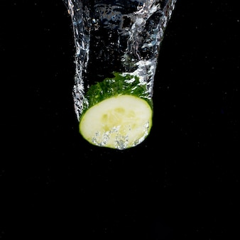 Cucumber with water splash falling on black background