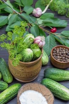 Огурцы и веточки укропа в деревянном ящике. душистый горошек, вишневые веточки, огурцы и соль в кокосовой скорлупе. домашние продукты ферментации