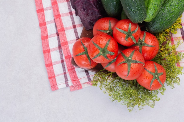 Cucumbers, greens and tomatoes on tablecloth