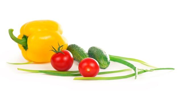 Огурцы, перец, помидоры и зеленый лук, изолированные на белой поверхности