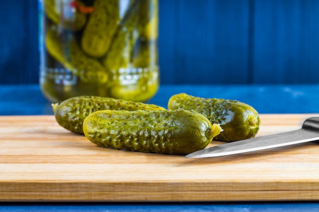 Cucumbers or pickled gherkins with a knife on a wooden cutting board. blue gray background.