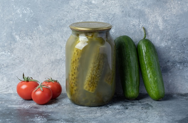 Cucumbers pickled in a glass jar on a marble background.