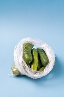 Cucumbers in plastic bag on blue background. stop using artificial food storage bags.