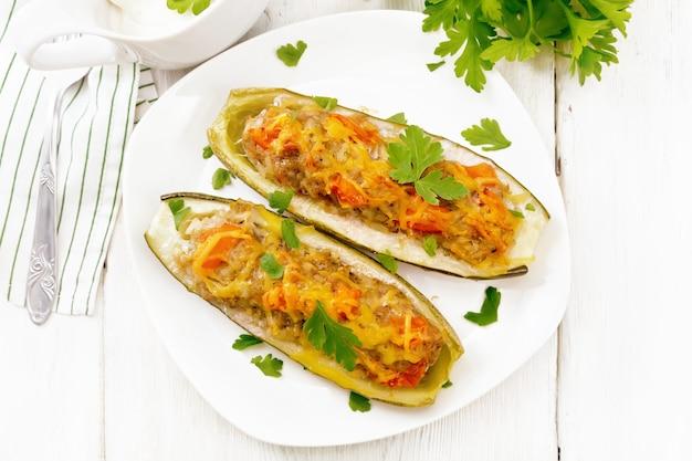 다진 고기, 토마토, 접시에 치즈, 파슬리를 넣은 후추, 그레이비 보트에 크림, 채소 소스, 위에서부터 가벼운 나무 판자 배경에 수건으로 속을 채운 오이