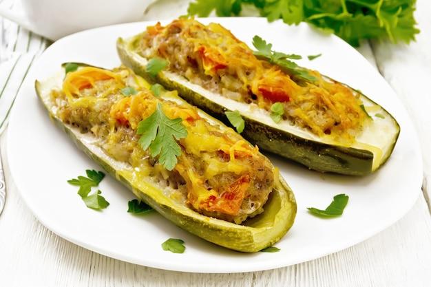 다진 고기, 토마토, 치즈와 파슬리를 접시에 넣은 후추, 그레이비 보트에 크림, 채소 소스, 가벼운 나무 판자 배경에 수건으로 속을 채운 오이