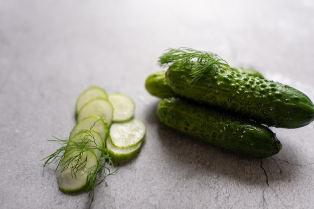 Cucumbers with dill on a gray background