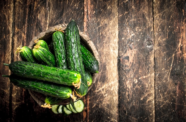 Cucumbers in a wooden bucket. on a wooden background.