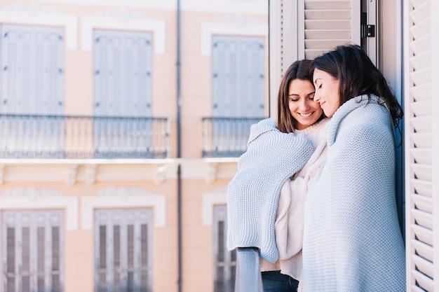 Обнимая женщин в плед на террасе