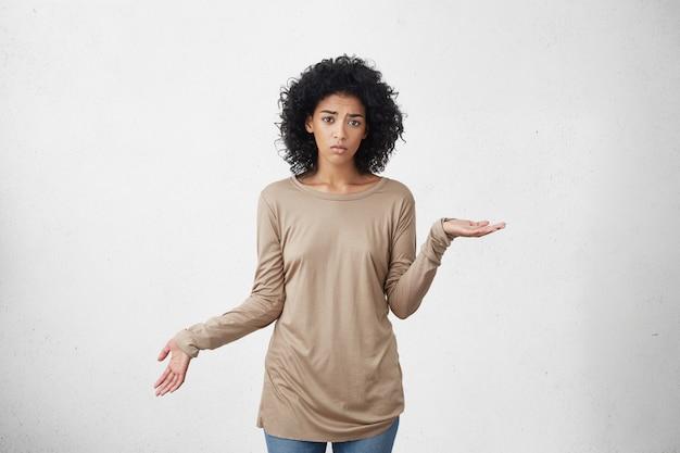Недоуменная озадаченная темнокожая женщина жестикулирует руками в невежестве и растерянности, пожимая плечами, словно говоря: не знаю, кого это волнует и что. негативные чувства, жизненное восприятие и отношение