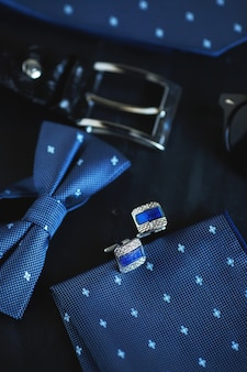 Cufflinks on the black surface. gentlemen accessories close up.