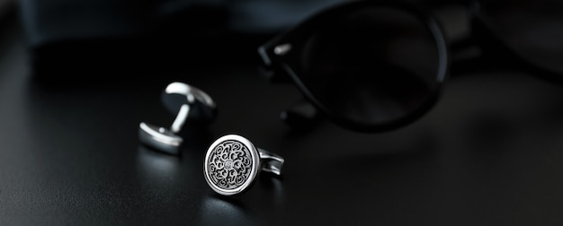 Cufflinks with sunglasses on black surface
