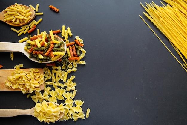 マカロニは、黒の背景に分離しました。cuisineの概念。