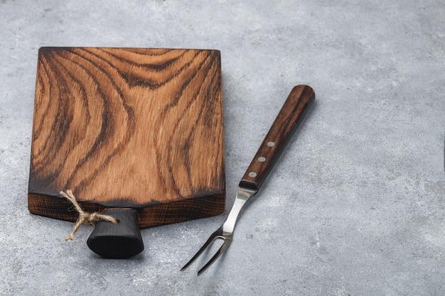 料理の背景。まな板天然木と肉用フォーク。コピースペース