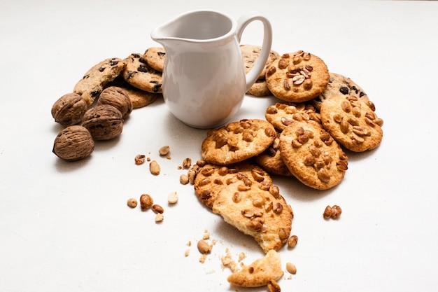 유기농 과자 가게의 요리 배경. 땅콩과 초콜릿 화이트 테이블에 우유의 투 수 주위에 누워 wholegrain 스콘. 쿠키와 함께 맛있는 아침 식사의 개념