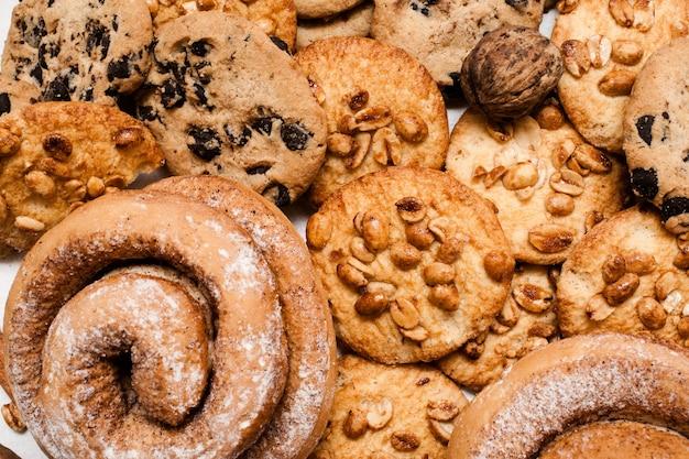 과자의 요리 배경을 닫습니다. 땅콩과 초콜릿이 들어간 wholegrain 쿠키, 설탕 가루와 함께 구운 롤, 평면도. 맛있는 수제 과자, 다이어트, 탄수화물 개념 해체