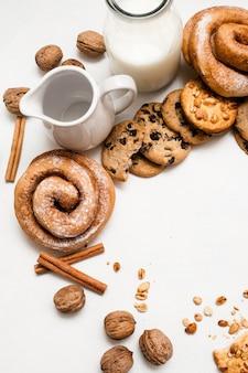 생과자 음식, 상위 뷰 여유 공간의 요리 배경. 통 곡물 스콘과 구운 롤, 호두와 계피가 우유 병과 투수 근처에 놓여 있습니다. 맛있는 아침 식사의 개념