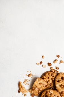 땅콩과 wholegrain 쿠키의 요리 배경입니다. 흰색 테이블에 맛있는 수제 과자, 여유 공간이있는 평면도를 닫습니다.