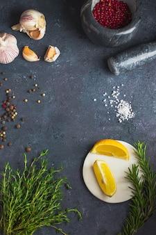 料理の背景。さまざまなスパイス、ハーブレモン、塩、タイム、ピンクコショウ、ローズマリー、ニンニクのセット。黒い石の背景に。コピースペースとflatlay。テンプレートフードブログソーシャルメディア。