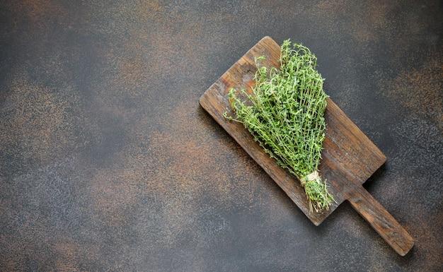 Кулинарный фон со свежим тимьяном на деревянной доске в деревенском стиле, винтажный темный фон
