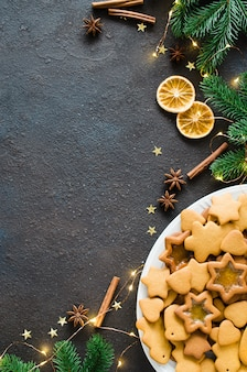 Culinary background with freshly baked christmas gingerbread, spices and fir branches.