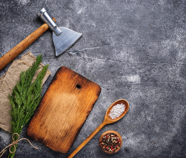 Culinary background with spices, cutting board and hatchet