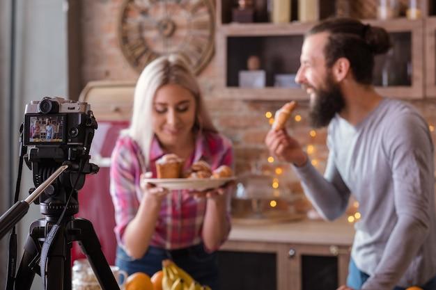 요리 블로그. 베이킹 취미. 커플 촬영 비디오 튜토리얼. 신선한 케이크와 파이를 가진 남자와 여자.