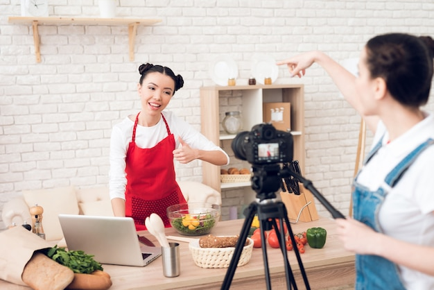 Culinary bloggers read from laptop with one girl.