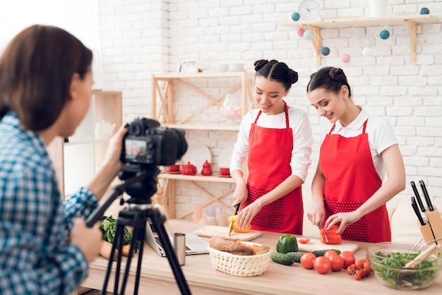 Culinary bloggers in red aprons dicing peppers with camera