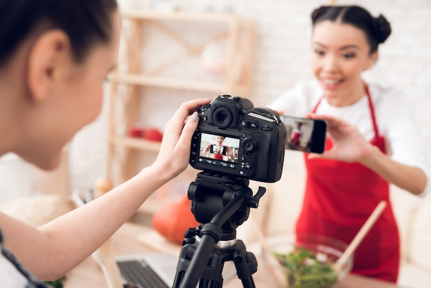 Culinary bloggers in red aprons taking selfie with one girl