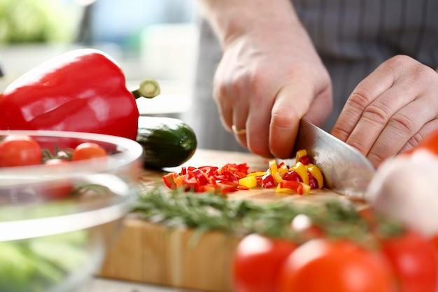 料理長が唐辛子のみじん切りの小さなスライス。木の板の鋭いナイフによる材料を切る人。新鮮で健康的な食品。カラフルでおいしいダイエットサラダレシピ水平写真