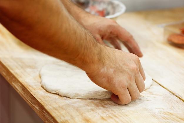 トマトピザを調理する料理人