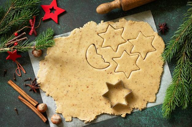 料理のクリスマスの背景。ジンジャーブレッド生地と材料。コピースペースのある上面図フラットレイ背景。