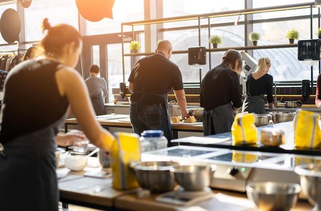 Кулинарный класс. вид сзади процесса приготовления. разные люди в серых фартуках на кухне учатся готовить