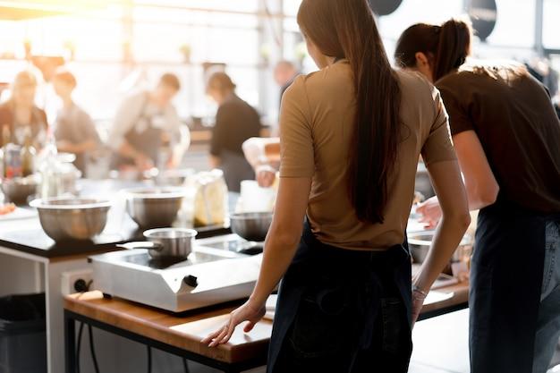 Кулинарный класс. вид сзади процесса приготовления. разные неузнаваемые люди в серых фартуках на кухне учатся готовить. кулинарная мастерская. готовить обучение
