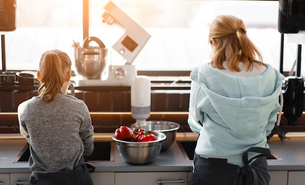 Кулинарный класс. две девушки готовят овощи на кухне. фото со спины
