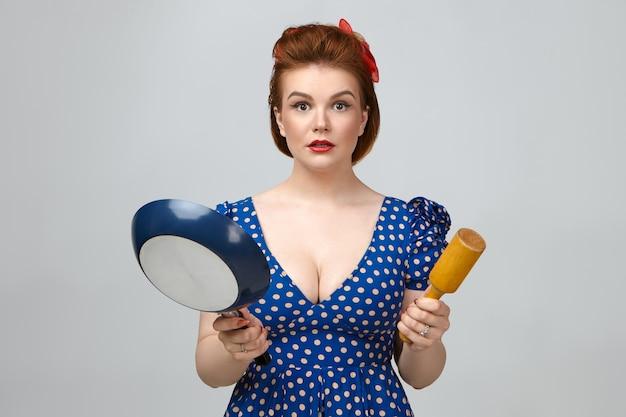 Culinario e cucina. stupita bella giovane casalinga caucasica che indossa un abito punteggiato vintage con taglio basso fissando la telecamera con la bocca aperta, tenendo la padella e il mattarello