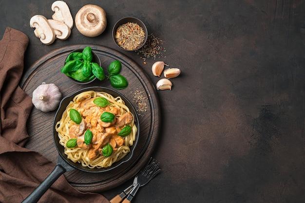 Кулинарный стол с пастой и сливочно-грибным соусом, базиликом, чесноком и специями на темно-коричневом столе. вид сверху, с местом для копирования
