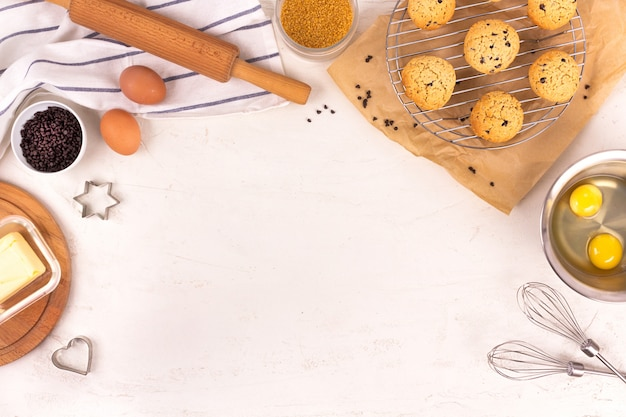 Culinary equipment and ingredients background. eggs, flour, sugar, chocolate, butter, bakeware. flat lay. copyspace.