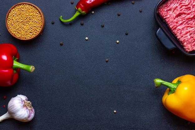 ミンチ肉コショウ調味料チェリートマトパプリカと暗い色合いの料理フレームの背景..。