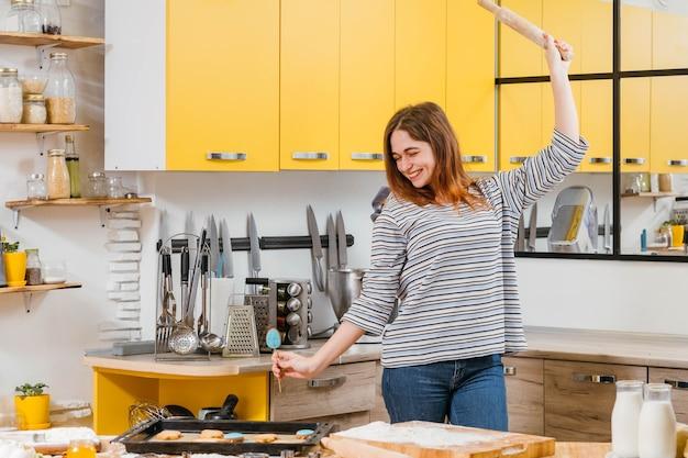 料理の趣味。キッチンで楽しんでいる女性、焼きたてのビスケットの周りに麺棒で踊り、笑顔。