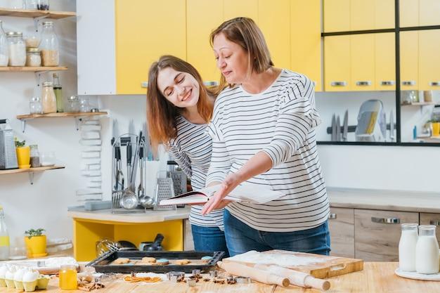 요리 취미. 엄마와 딸이 함께 요리를 즐기고 요리 책의 레시피와 결과를 비교합니다. 프리미엄 사진