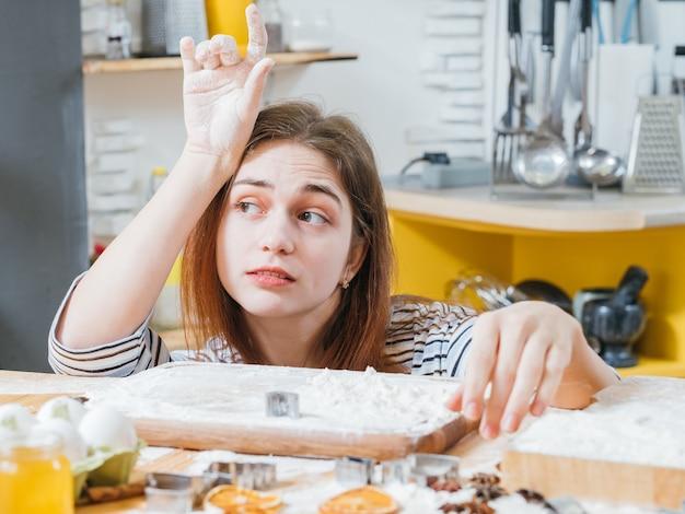 Кулинарный досуг. портрет скучающей дамы, сидящей на кухне за столом, покрытым мукой, в ожидании готового печенья.