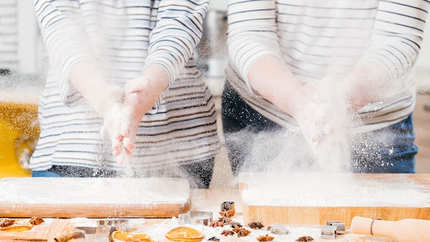Culinary master class. women slapping hands, shacking off flour.