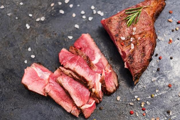 Кулинарный рецепт. ковбойский стейк. вид сверху нарезанной средней жареной говядины и смеси перцев.
