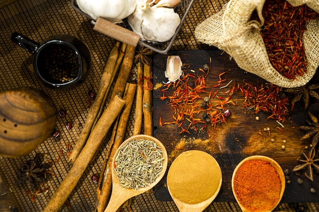 Culinary seasonings with herbs and spices on rustic background